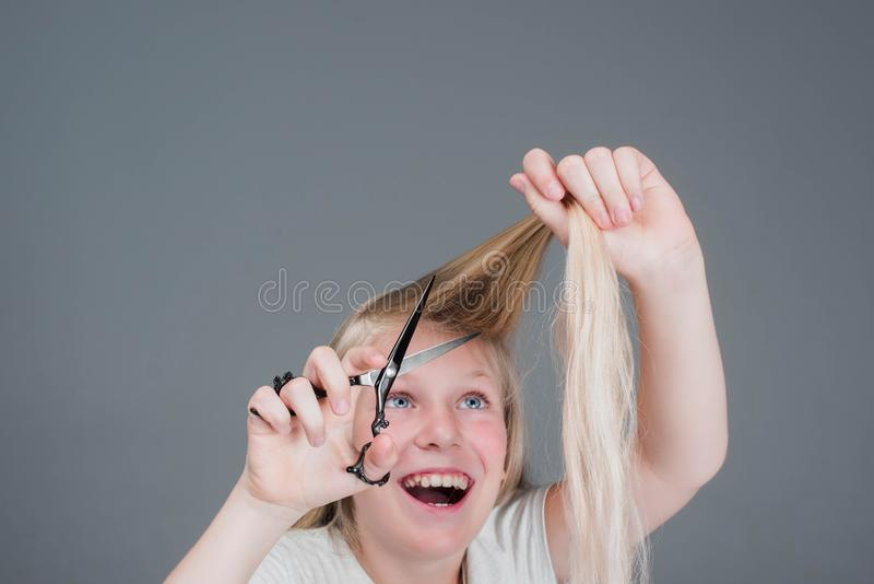 Attractive chaild girl is cutting her long blond natural hair stock photo