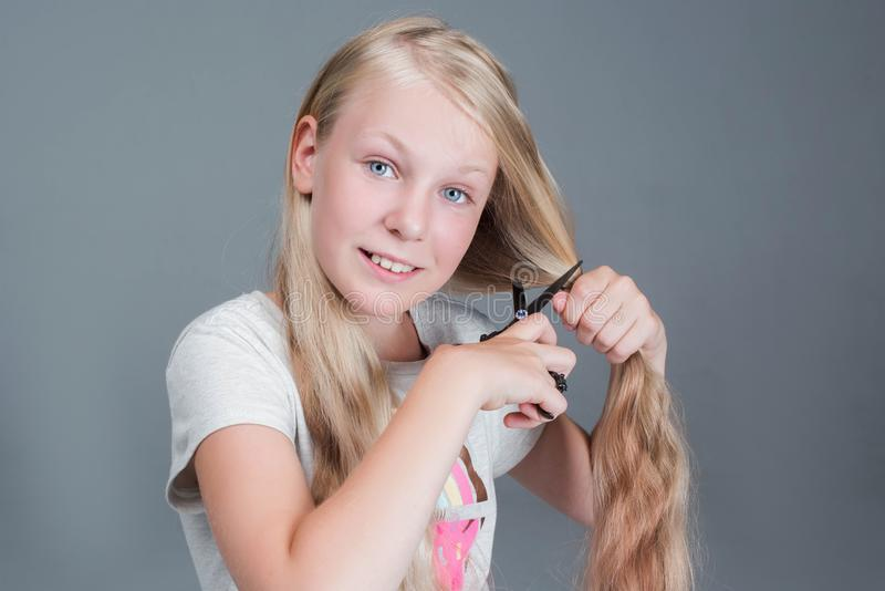 Attractive chaild girl is cutting her long blond natural hair stock image