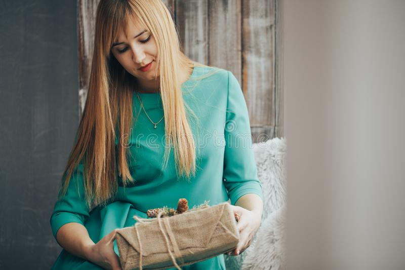 Attractive cheerful girl with playful look. Blonde hair beautiful woman with present in her hands. Young woman portrait stock photography
