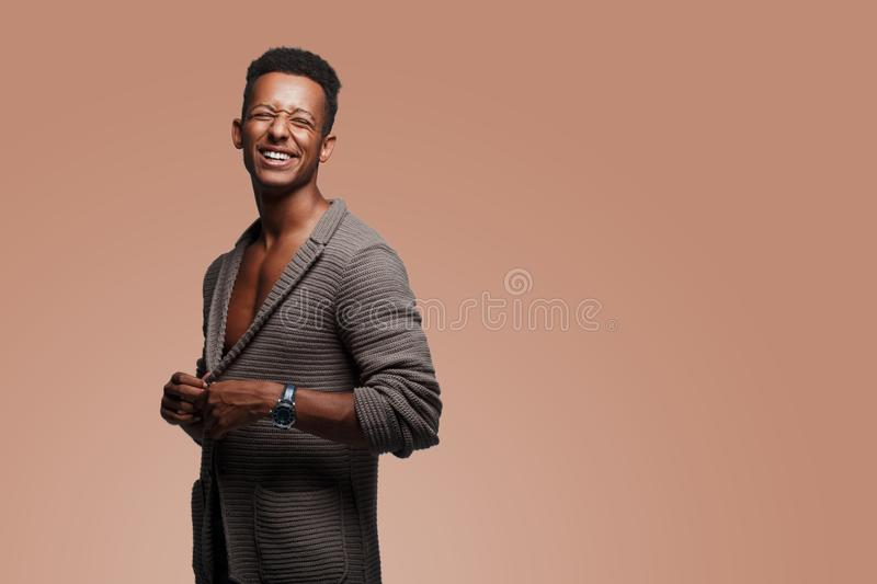 Funny mixed race man posing amusing in cardigan, with naked torso, shot in studio,  on a light brown background. stock photos