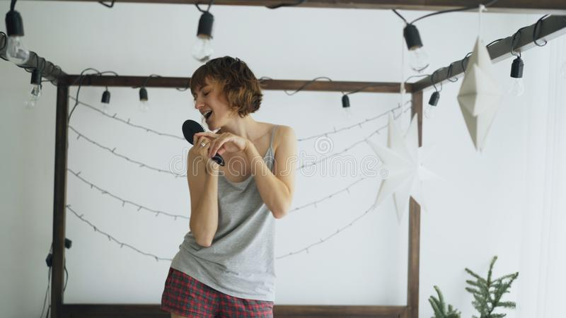 Attractive cheerful woman dancing on bed and singing with comb like microphone at home. In the morning stock photography