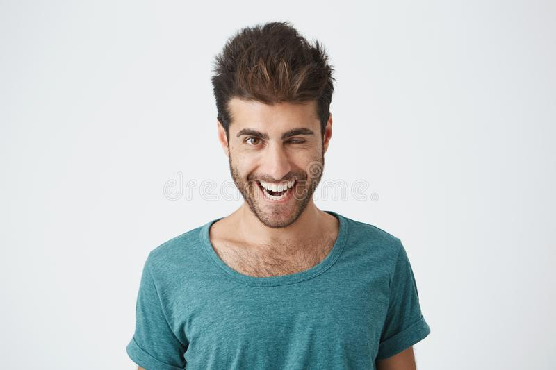 Attractive and cheerful young man with beard and stylish haircut wearing blue t-shirt blinking his eyes with pleasure stock image