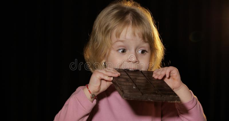 Attractive child eating a huge block of chocolate. Cute blonde girl royalty free stock image