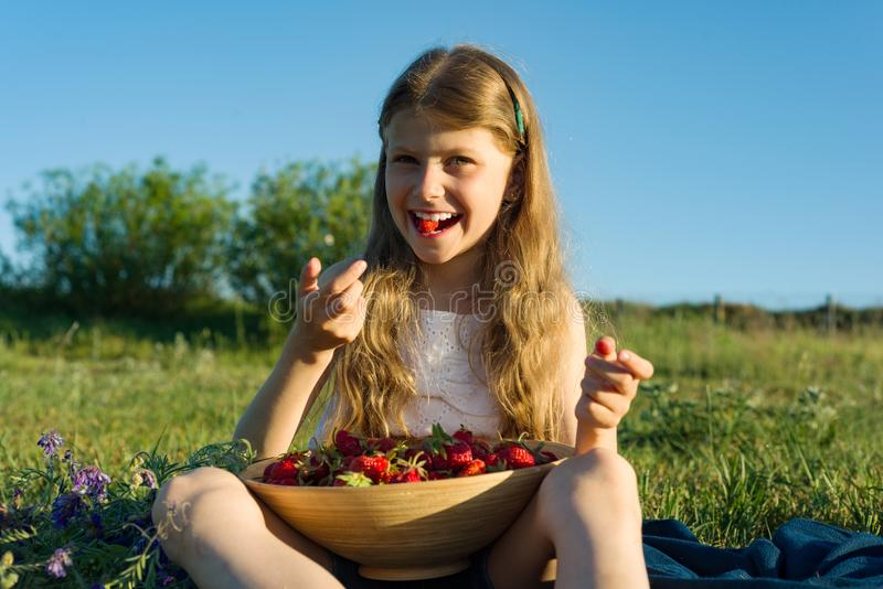 Attractive child girl eating strawberry. Nature background, green meadow, country style royalty free stock image