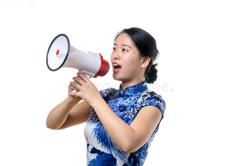 Attractive Chinese woman in traditional dress. Shouting into a loud hailer or megaphone at a rally or demonstration or when addressing a crowd public speaking royalty free stock photos