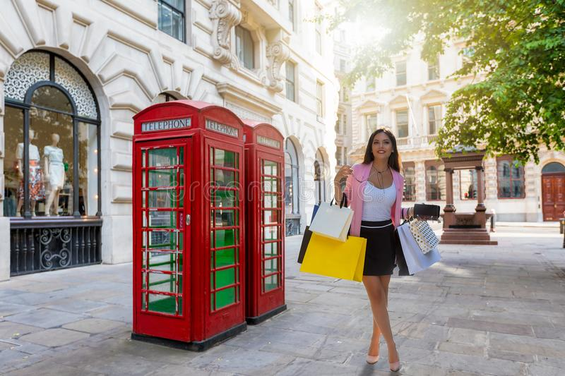 Attractive city shopping woman with bags in her hand in London stock images