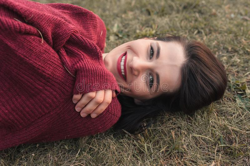 Attractive close up portrait of a beautiful young Caucasian woman smiling and looking at the camera, lying on the grass. royalty free stock images