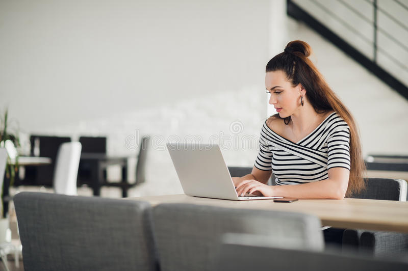 Attractive concentrated adult woman browsing the internet and searching information for business during lunchtime. Attractive concentrated adult woman browsing royalty free stock photo