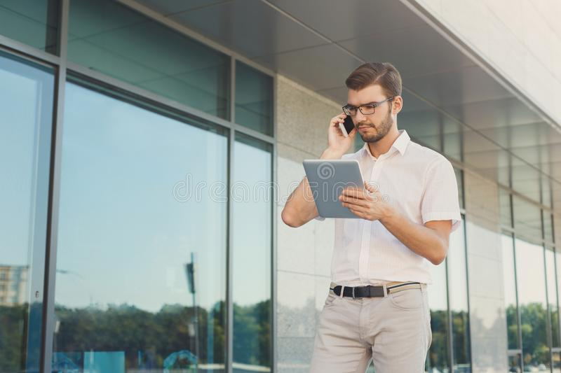 Pensive businessman using phone and tablet outdoors stock images
