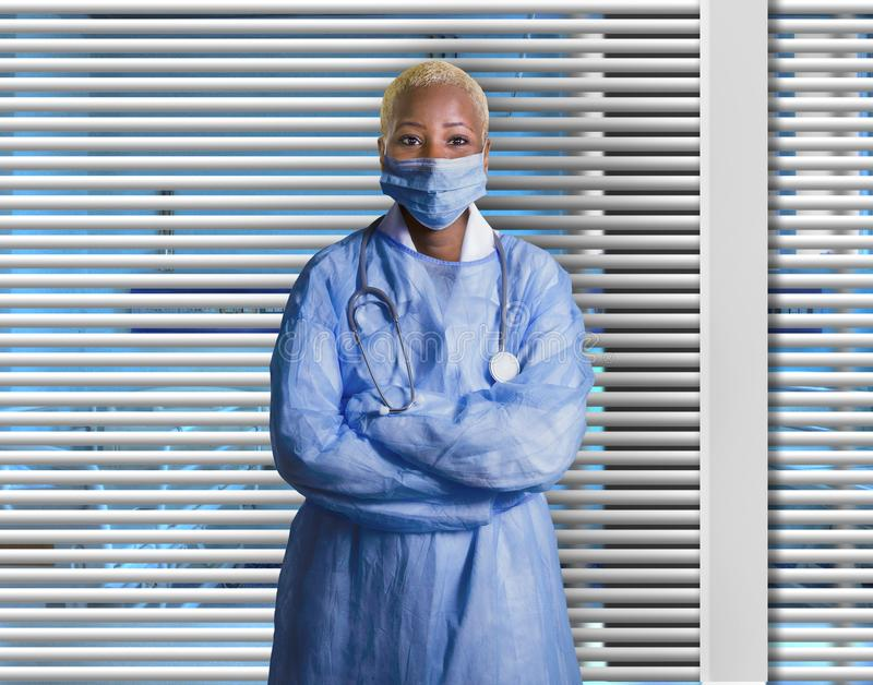 Attractive and confident black African American medicine doctor wearing face mask and blue scrubs standing corporate at. Young attractive and confident black stock image