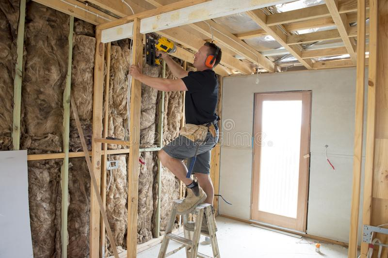 Attractive and confident constructor carpenter or builder man working wood with electric drill at industrial construction site stock photo