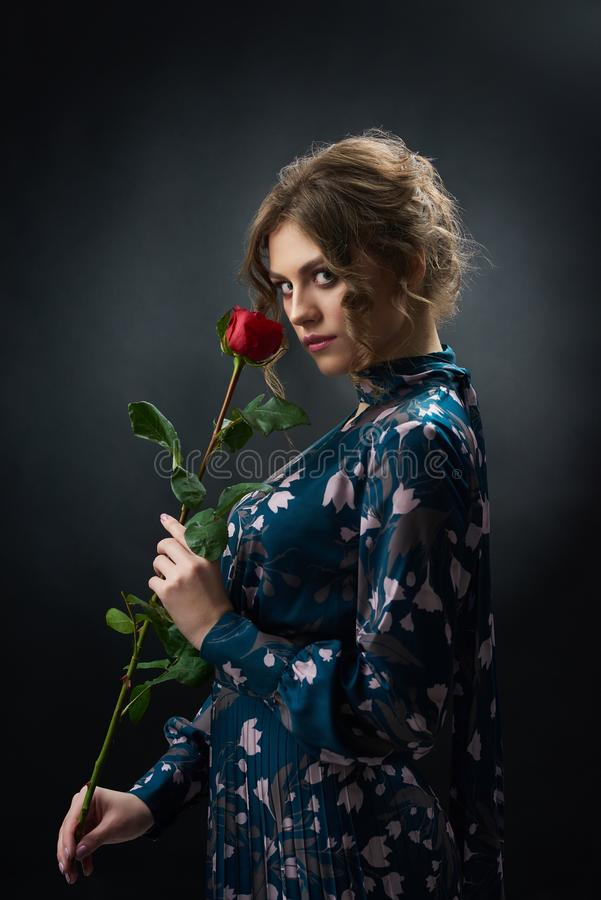 Attractive confident girl holding red rose. stock images