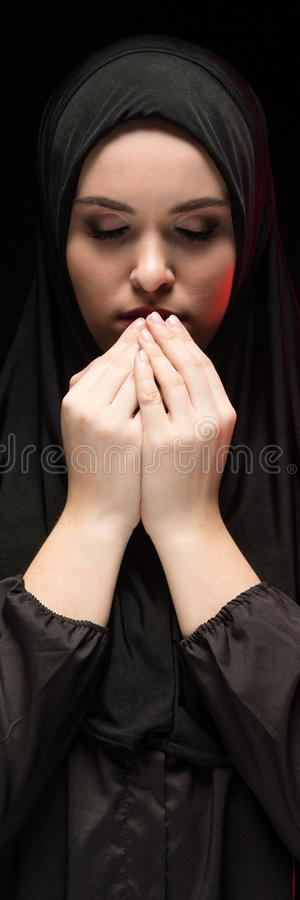 Portrait of beautiful serious young muslim woman wearing black hijab with hands near her face as praying concept on stock image