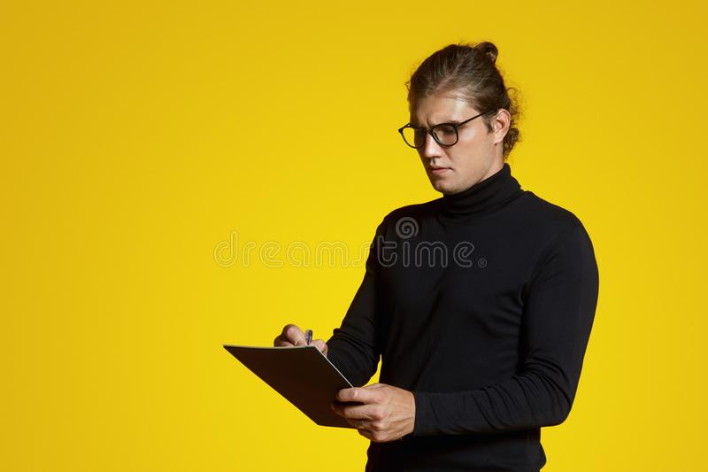 Attractive confident student with eyeglasses, wearing polo neck, makes notes in notepad and standing isolated over yellow backdrop. Handsome young man with stock photos