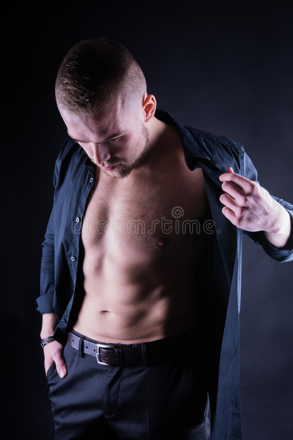 Attractive, Confident, young man with open shirt on muscular torso, ripped abs and pecs on black background. stock image