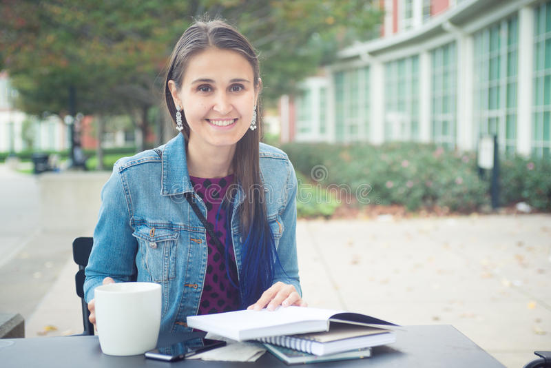 Attractive confident young woman reading book in street cafe stock photo