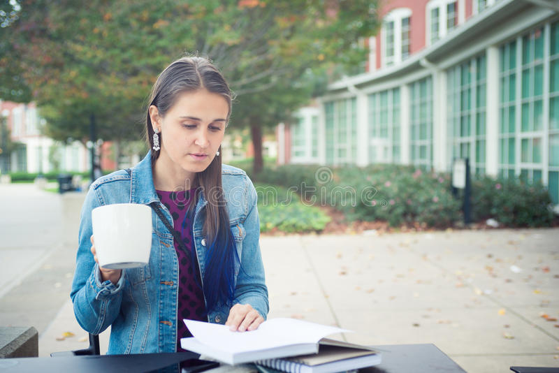 Attractive confident young woman reading book in street cafe royalty free stock images
