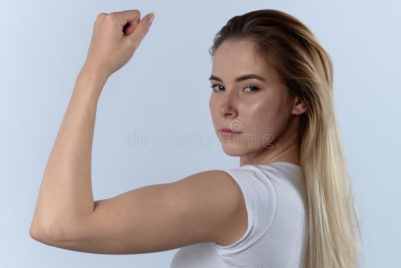 Attractive confident young woman shows biceps. Portrait on a whi stock images