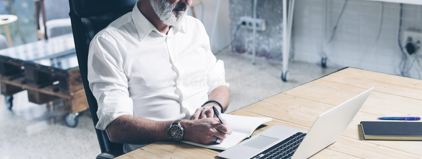 Attractive and confidental adult businessman using mobile laptop computer while working at the wooden table at modern stock photos
