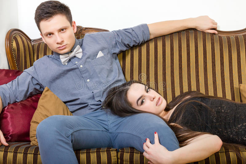 Attractive couple at ancient room sitting on couch or sofa. Pair of lovers in living playing. Persons in luxury home interior. Attractive couple at ancient room stock photos
