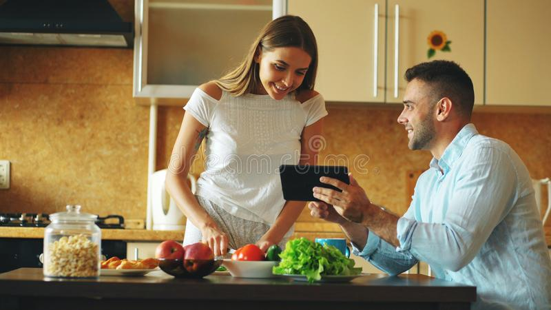 Attractive couple chatting in the kitchen early morning. Handsome man using tablet while his girlfriend cooking stock images