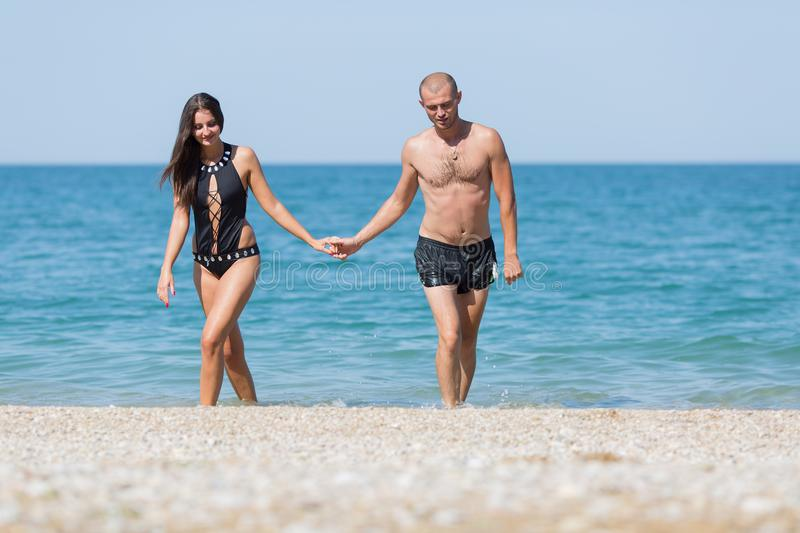 Attractive couple come from sea holding hands royalty free stock photo