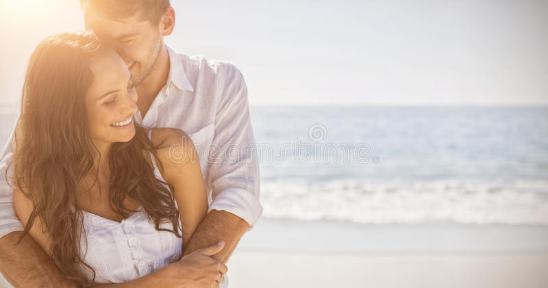 Attractive couple cuddling. At the beach royalty free stock image
