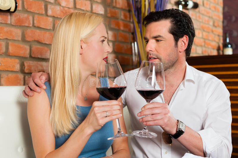 Attractive couple drinking red wine in restaurant or bar. Attractive young couple drinking red wine in restaurant or bar, it might be the first date royalty free stock image