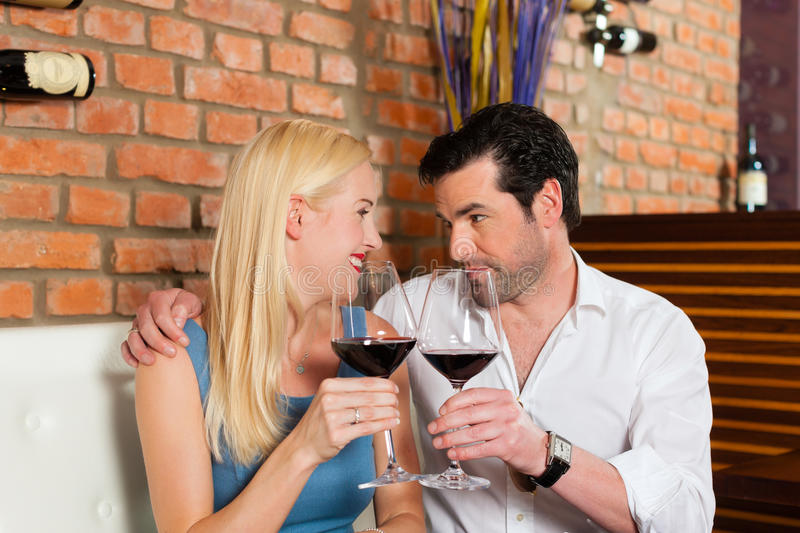Attractive couple drinking red wine in restaurant or bar. Attractive young couple drinking red wine in restaurant or bar, it might be the first date royalty free stock photography