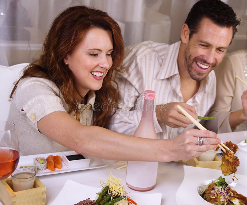 Attractive couple eating at restaurant, stock photos