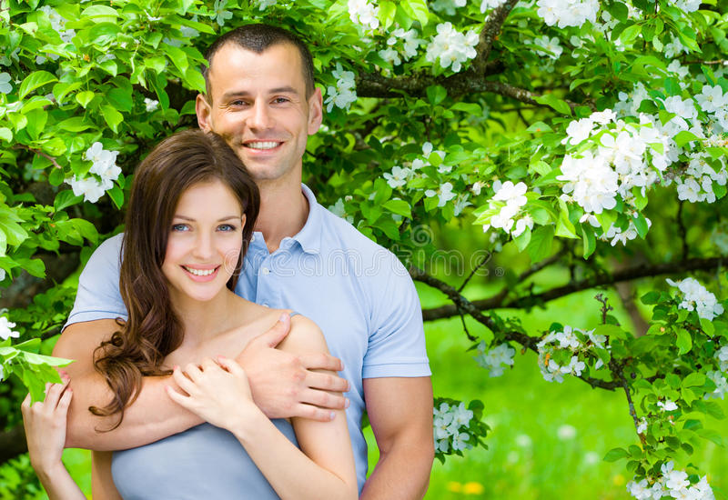 Attractive couple embracing near blossomed tree. Pretty couple embracing near blossomed tree in the park. Concept of love and stable relations stock photos