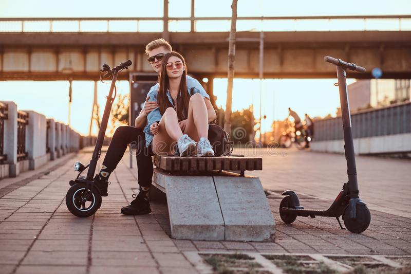 Attractive couple enjoying sunset with their scooters. Young beautiful romantic couple with electric scooters is sitting on the bench near brige at sunset time royalty free stock images