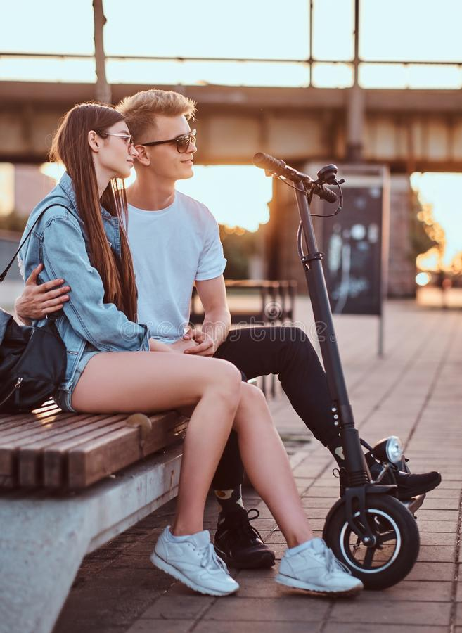 Attractive couple enjoying sunset with their scooters. Young beautiful romantic couple with electric scooters is sitting on the bench near brige at sunset time stock images
