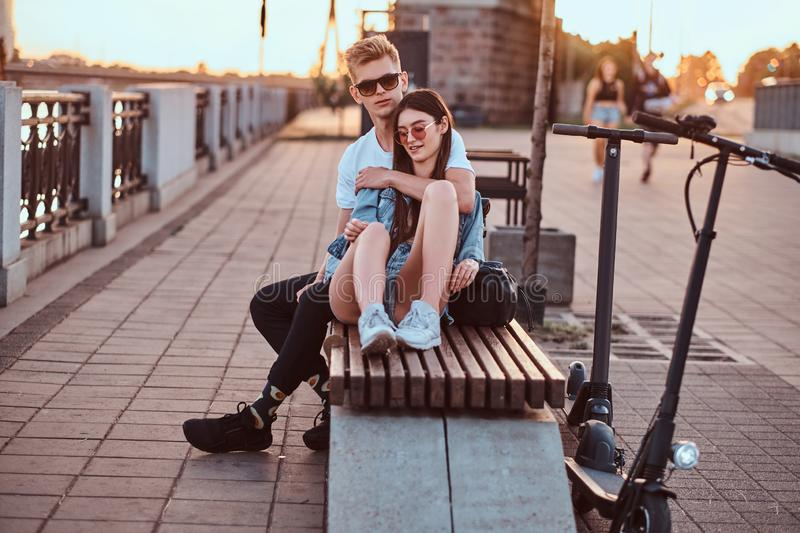 Attractive couple enjoying sunset with their scooters. Young beautiful romantic couple with electric scooters is sitting on the bench near brige at sunset time royalty free stock image