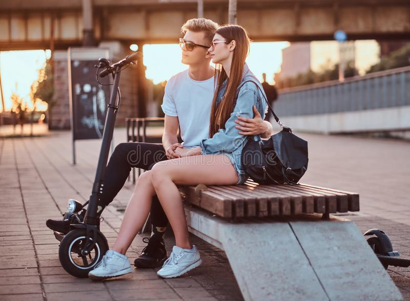 Attractive couple enjoying sunset with their scooters. Young beautiful romantic couple with electric scooters is sitting on the bench near brige at sunset time stock photography