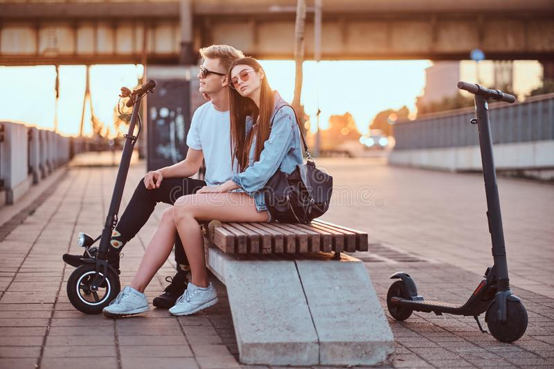 Attractive couple enjoying sunset with their scooters. Young beautiful romantic couple with electric scooters is sitting on the bench near brige at sunset time stock image