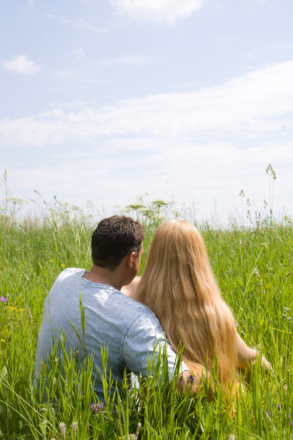 Attractive couple enjoying togetherness on meadow. Summer day stock image