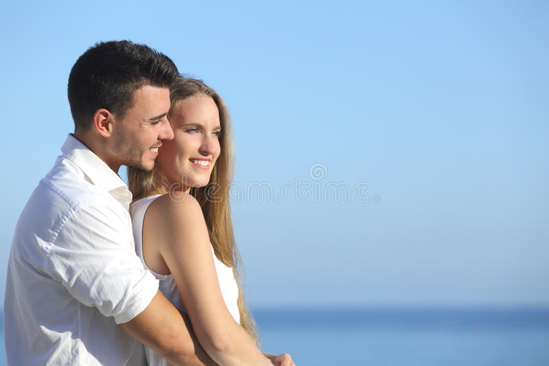 Attractive couple flirting and cuddling looking ahead. With the sea in the background stock images