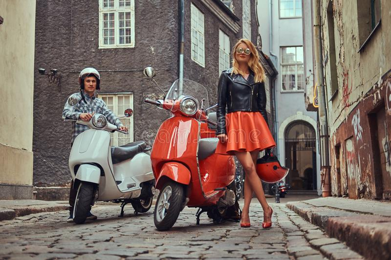 Attractive couple, a handsome man and female standing on an old street with two retro scooters. stock image