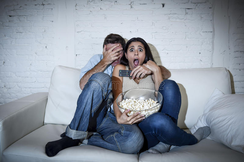 Attractive couple having fun at home enjoying watching television horror movie show. Young happy attractive couple having fun at home enjoying watching stock image