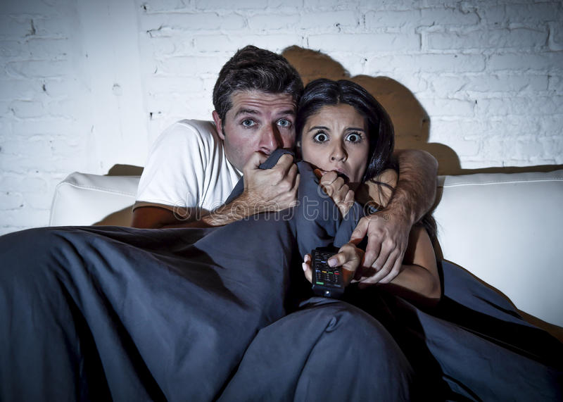 Attractive couple at home enjoying watching television horror movie covering with blanket royalty free stock image