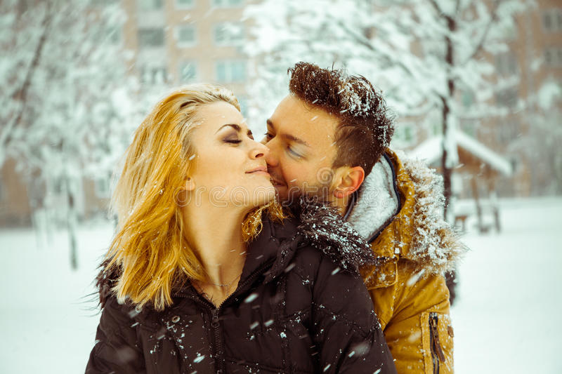 Attractive couple hugging each other in the snow outdoors stock photography