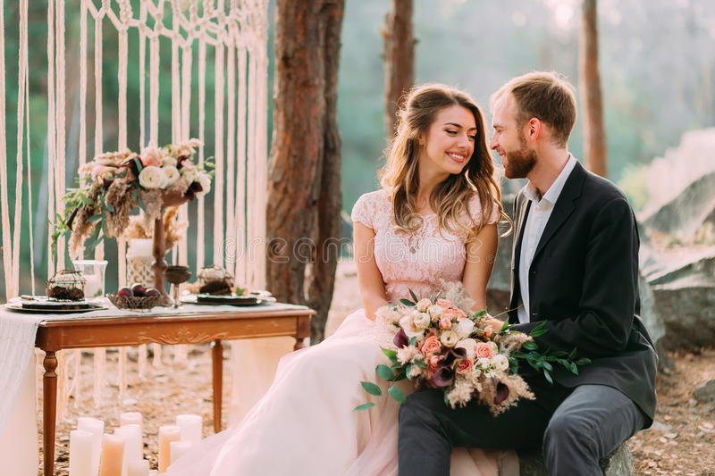 Attractive couple newlyweds bride and groom laughs and smiles to each other, happy and joyful moment. Man and woman in. Festive clothes sit on the stones royalty free stock image
