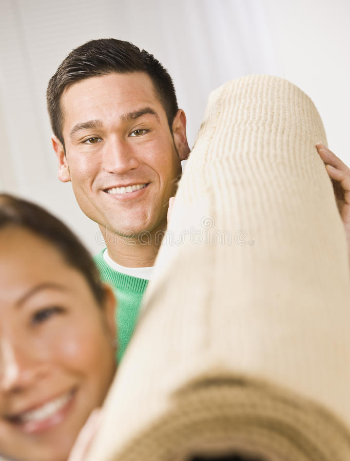Attractive Couple with Roll of Carpet royalty free stock photos