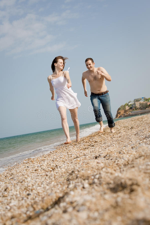 Attractive Couple Is Running Along The Beach Stock Image