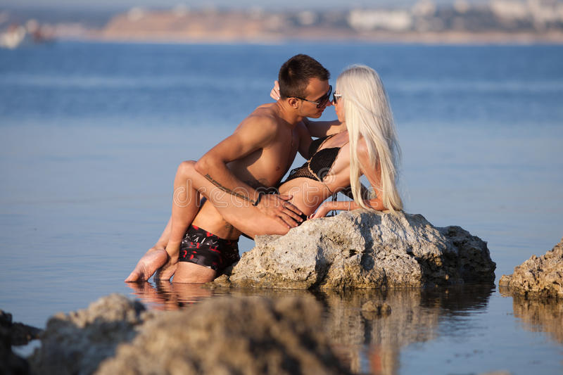 Attractive couple at the sea. Young men and women in swimwear flirting and kissing on wild rock at the sea royalty free stock photo