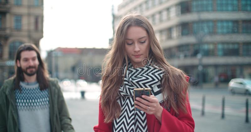 Young woman waiting for her boyfriend and typing on phone. stock photos