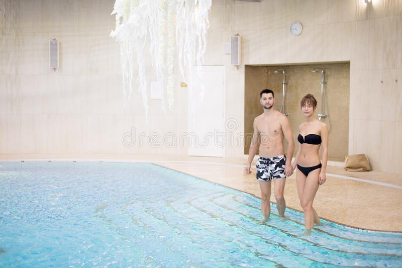 Attractive couple srtanding in the pool and looking at the camera stock images