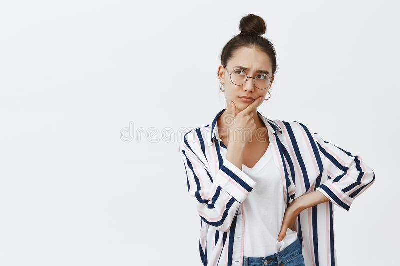 Attractive creative woman making up new idea for future design. Indoor shot of thoughtful focused young female, touching. Jaw and looking left with concentrated royalty free stock photos
