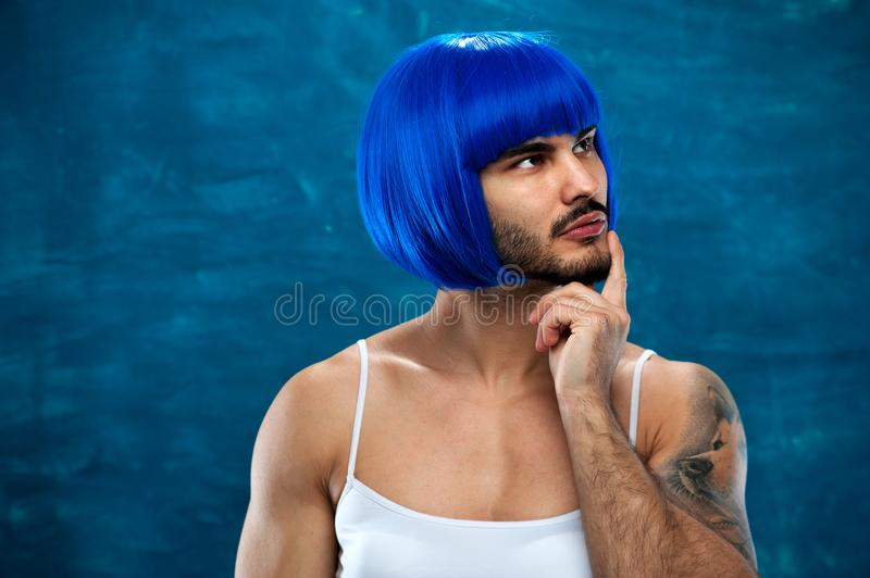 Attractive cross dressing male person in blue wig. Attractive cross dressing male person wearing female clothes and blue wig posing on blue backdrop royalty free stock photo